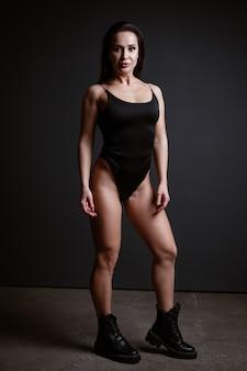 Sportieve slanke vrouw poseren in zwarte romper op zwarte achtergrond
