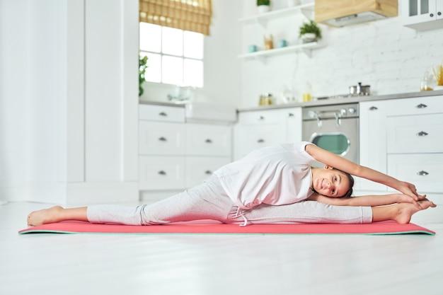 Sportieve spaanse tiener die sportkleding draagt en naar de camera kijkt, splitst terwijl ze haar lichaam thuis op een mat uitrekt. training, gezond levensstijlconcept. zijaanzicht