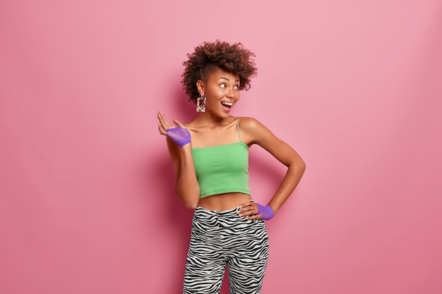 Sportieve tevreden donkere vrouw houdt de hand op de taille, gekleed in een bijgesneden top en legging, draagt sporthandschoenen, lacht vrolijk, kijkt opzij