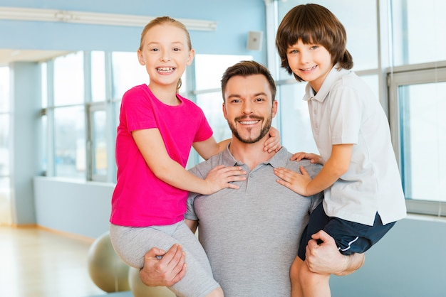 Sportieve vader met kinderen. vrolijke jonge sportieve vader die zijn kinderen in handen draagt en glimlacht terwijl hij in de sportclub staat