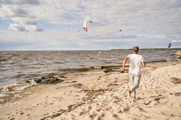 Sportieve volwassen man die een zonnige dag buiten in de natuur doorbrengt en alleen langs de kust rent