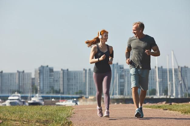 Sportieve volwassen paar in koptelefoon glimlachen naar elkaar terwijl u geniet van samen joggen in de stad