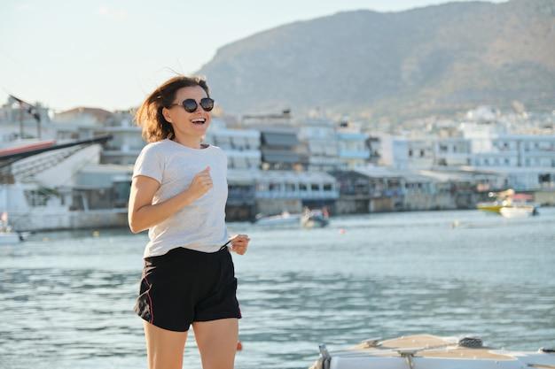 Sportieve volwassen vrouw joggen draait op promenade