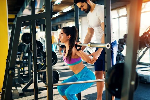Sportieve vorm meisje doet squats in de sportschool met bar en haar personal trainer.