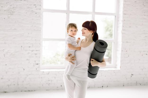 Sportieve vrij jonge moeder met weinig babymeisje in witte sportslijtage en yogamat in handen