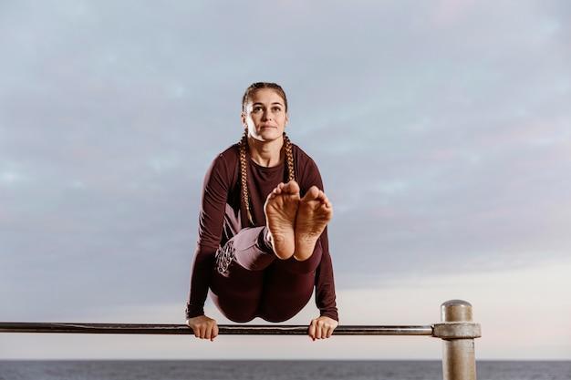 Sportieve vrouw aan het strand die geschiktheidsoefeningen doet