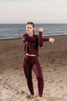 Sportieve vrouw aan het strand die zich uitstrekt