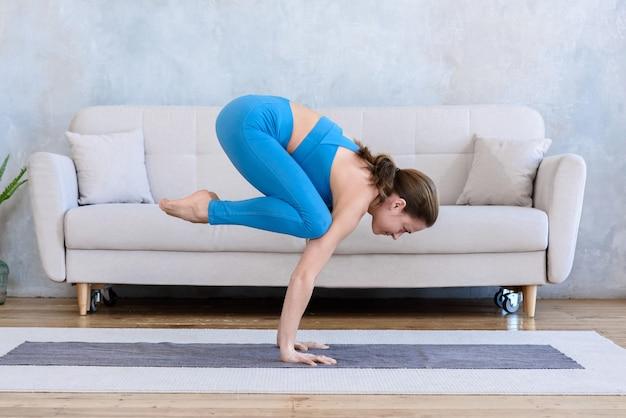 Sportieve vrouw beoefenen van yoga thuis op mat duif pose doen