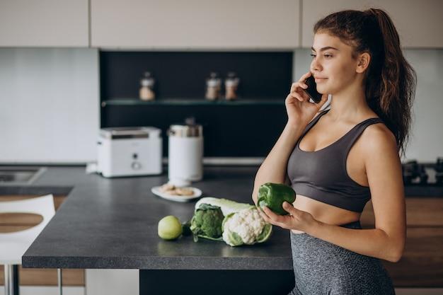Sportieve vrouw bij keuken met behulp van mobiele telefoon