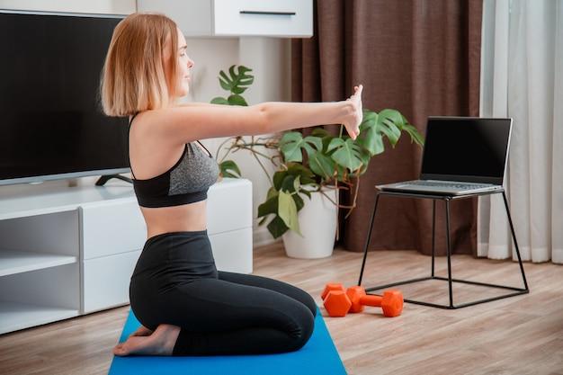 Sportieve vrouw die dumbbells gebruikt die thuis fitness maken via laptop via een videogesprek op afstand online jonge vrouw afvallen door online sportschooltraining op afstand