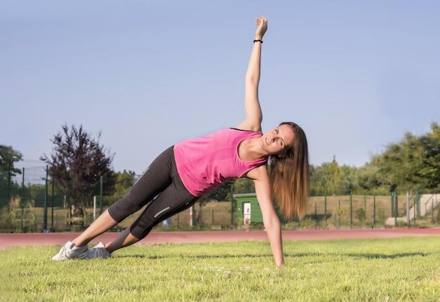 Sportieve vrouw die een training in een park doet - sport en gezond levensstijlconcept