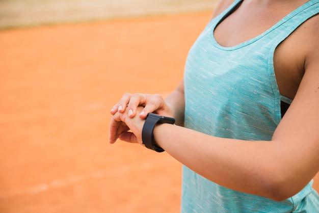 Sportieve vrouw die fitnesstracker bekijkt