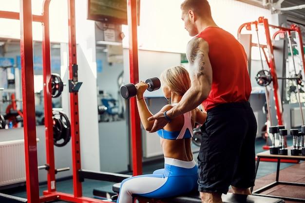 Sportieve vrouw die gewichtsoefeningen met hulp van haar persoonlijke trainer doet bij gymnastiek