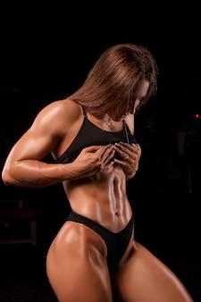 Sportieve vrouw die haar afgezwakte buikspieren bekijkt