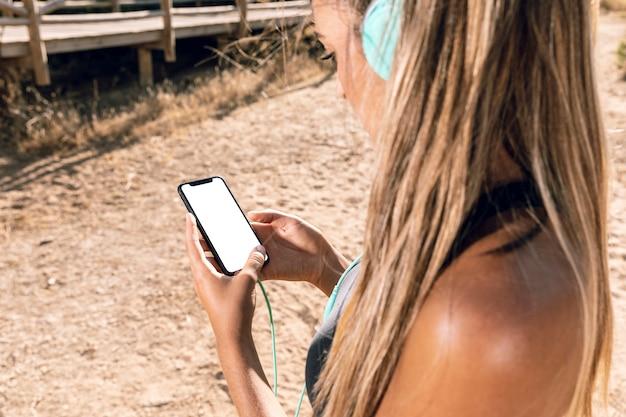 Sportieve vrouw die haar telefoonmodel bekijkt