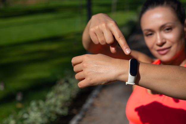 Sportieve vrouw die haar vinger op een fitnesstracker zet.