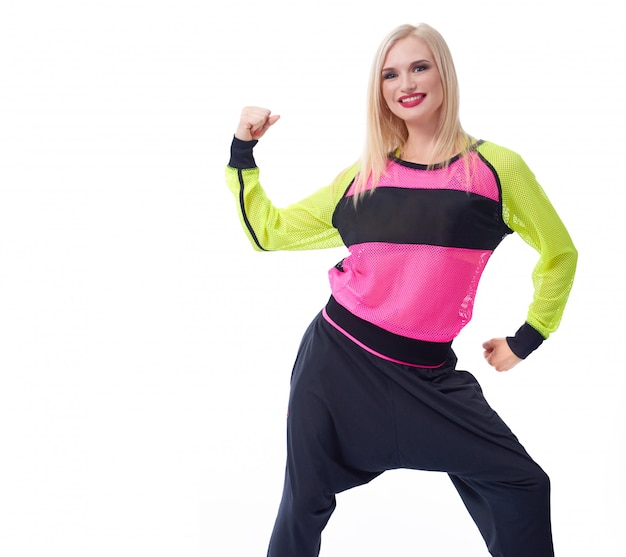 Sportieve vrouw die lacht met haar biceps haar arm buigen