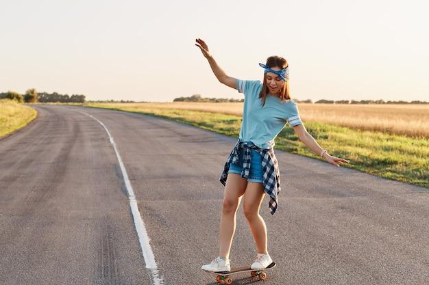 Sportieve vrouw die op het skateboard op de weg rijdt., slanke sportieve vrouw die geniet van longboarden, handen opsteken, een gelukkige geconcentreerde uitdrukking hebben, een gezonde levensstijl, ruimte kopiëren.