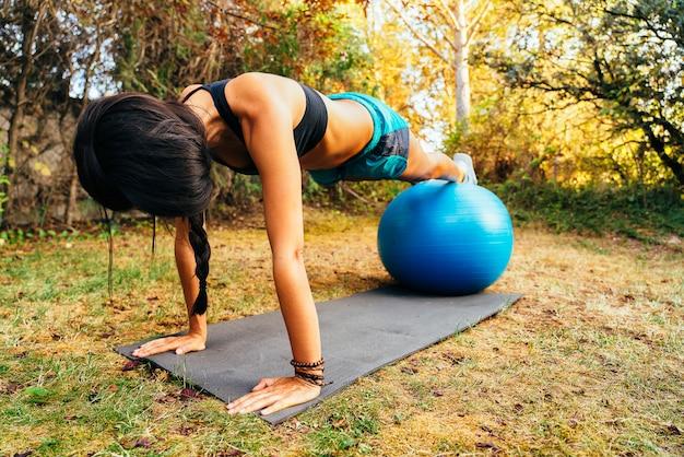Sportieve vrouw die pilates oefening met geschikte bal doet bij tuin.