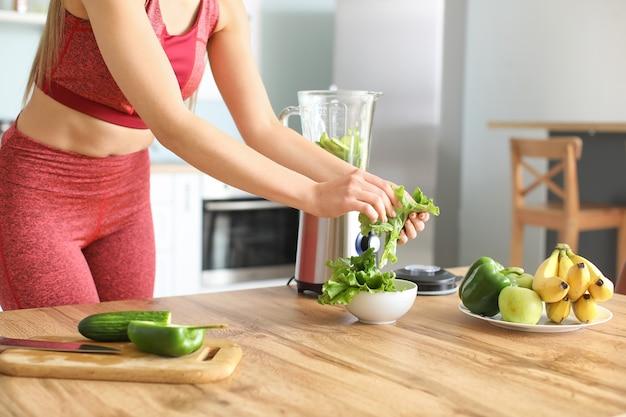 Sportieve vrouw die thuis smoothie in keuken maakt