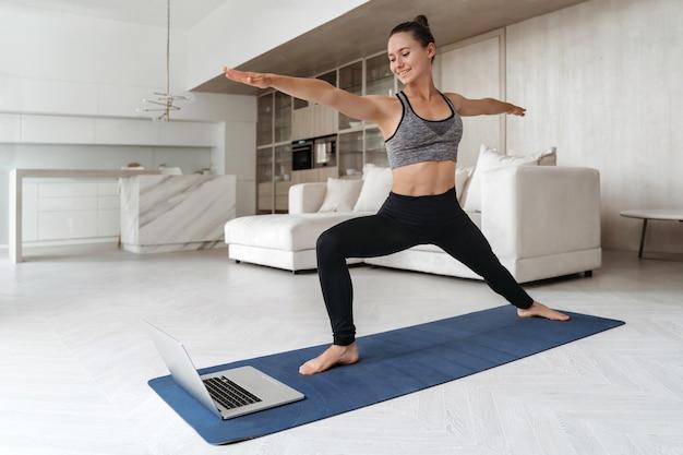 Sportieve vrouw die thuis yoga beoefent vanwege sociale afstand, met behulp van laptop voor online les