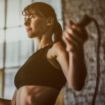 Sportieve vrouw die traint met springtouw in de sportschool