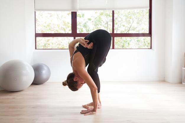 Sportieve vrouw die yoga beoefent in een lichte loft studio