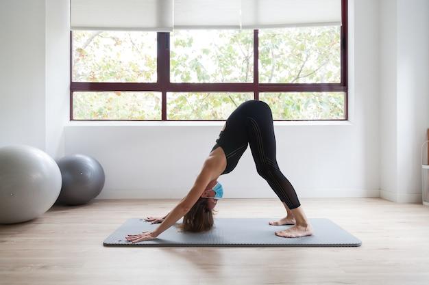 Sportieve vrouw die yoga beoefent met beschermend masker tijdens covid-19