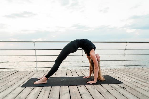 Sportieve vrouw die yogaasana op het overzees in de ochtend doet