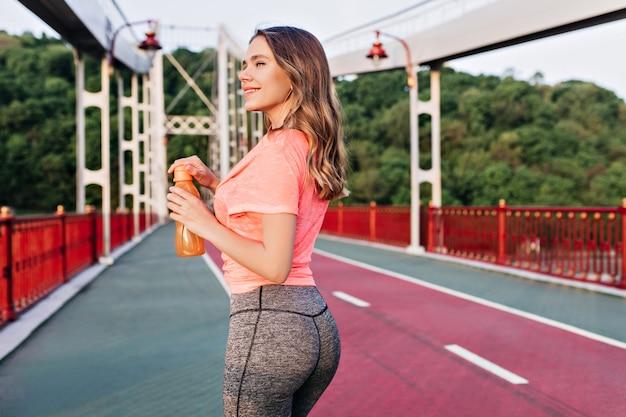 Sportieve vrouw die zich bij sintelspoor met vrolijke glimlach bevindt. opgewonden blond meisje genieten van training in zomerdag.