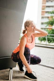 Sportieve vrouw die zich uitstrekt in de stedelijke omgeving