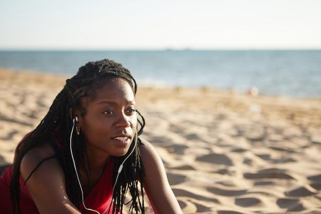 Sportieve vrouw die zich uitstrekt op het strand