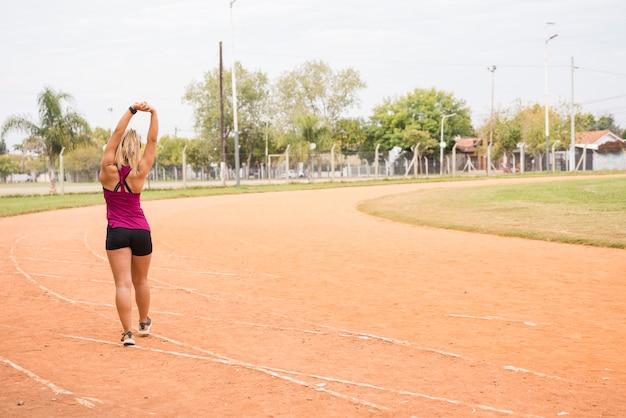 Sportieve vrouw die zich uitstrekt over stadion bijhouden