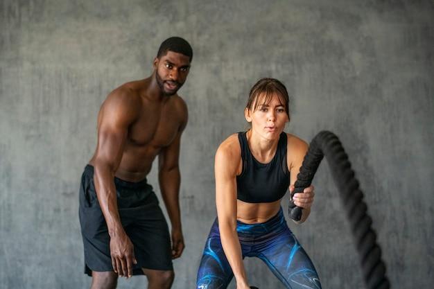 Sportieve vrouw doet een gevechtstouw in een sportschool met trainer