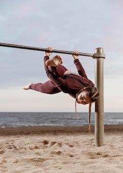Sportieve vrouw doet fitness oefeningen buiten aan het strand
