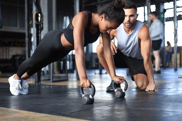 Sportieve vrouw doet push-up in een sportschool, haar vriendje kijkt naar haar.