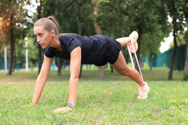 Sportieve vrouw doet squats met fitness gom expander in het park buiten.