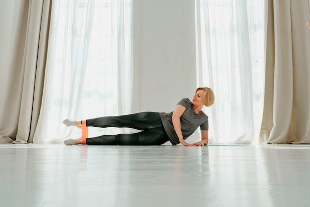 Sportieve vrouw doet thuis opwarmende oefening met elastiek