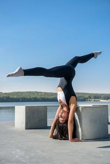 Sportieve vrouw doet yoga oefening in het park, in de buurt van het meer overdag. gezond levensstijlconcept