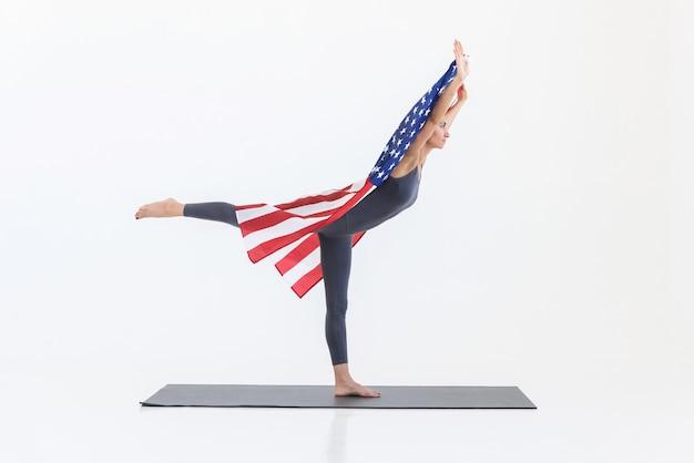 Sportieve vrouw doet yoga-oefeningen op de mat terwijl ze staan
