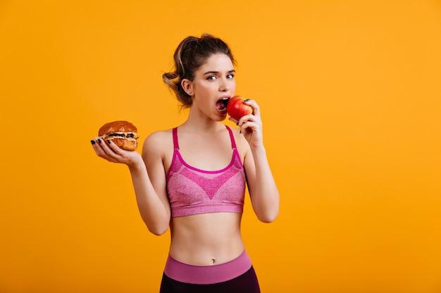 Sportieve vrouw eet rode appel op oranje muur