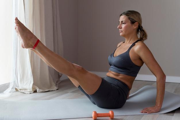 Sportieve vrouw in blauwe fitnesskleding zijwaarts