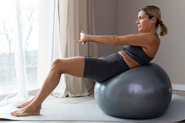 Sportieve vrouw in blauwe fitnesskleren die naast een geschiktheidsbal zitten