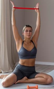 Sportieve vrouw in blauwe fitnesskleren die toebehoren gebruiken