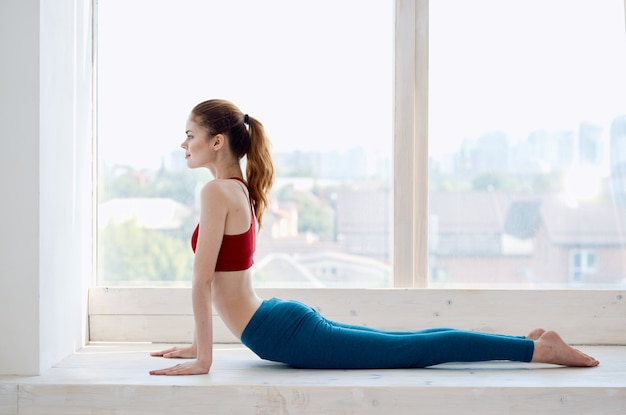 Sportieve vrouw in de buurt van venster meditatie levensstijl fitness