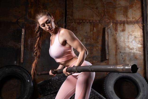 Sportieve vrouw in een roze top en legging doen oefening op biceps met een bar in de vorm van een metalen pijp in de sportschool garage.
