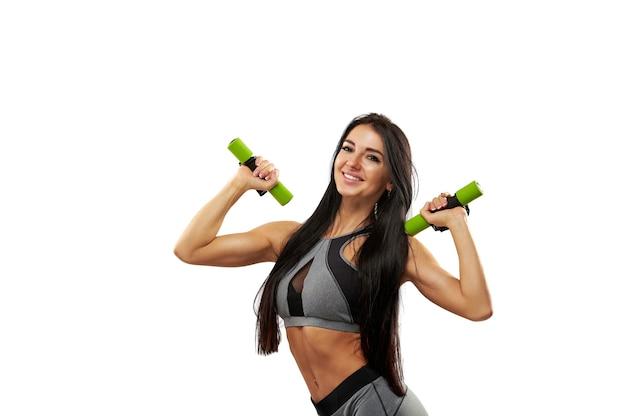 Sportieve vrouw in grijze sportkleding poseren en lachend naar de camera tijdens het pompen van schouderspieren en biceps. geïsoleerd op een witte achtergrond.
