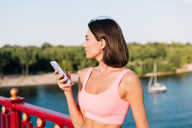 Sportieve vrouw in het passen van sportkleding bij zonsondergang bij moderne brug met uitzicht op de rivier, blije positieve glimlach met mobiele telefoon kijk opzij