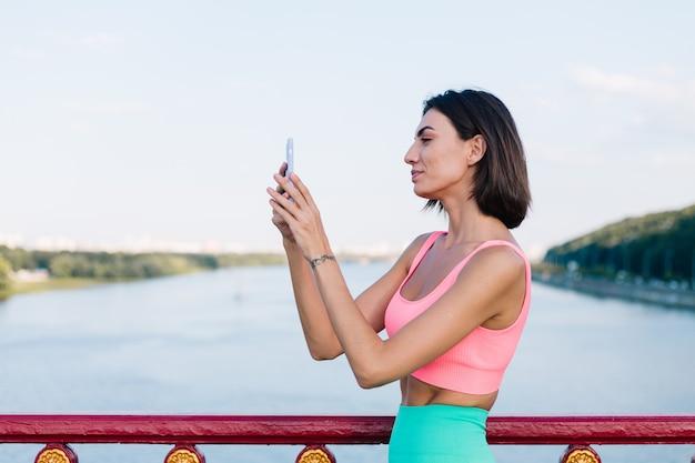 Sportieve vrouw in het passen van sportkleding bij zonsondergang bij moderne brug met uitzicht op de rivier, blije positieve glimlach met mobiele telefoon