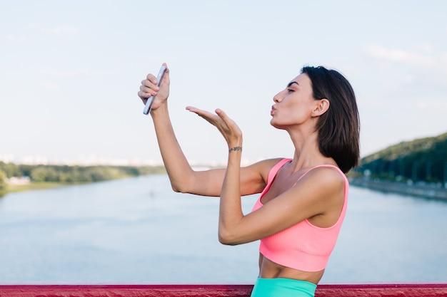 Sportieve vrouw in het passen van sportkleding bij zonsondergang bij moderne brug met uitzicht op de rivier gelukkige positieve glimlach met mobiele telefoon neem foto selfie video voor sociale verhalen